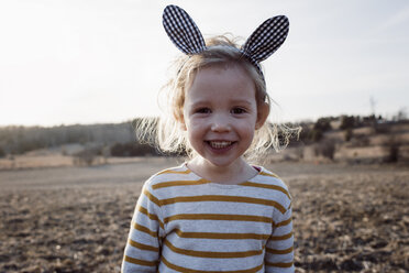 Portrait of cute cheerful girl wearing rabbit ears headband while standing on field during sunset - CAVF58359