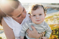Portrait of cute son carried by mother at beach - CAVF58368