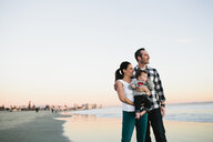 Family looking at view while standing against clear sky at beach during sunset - CAVF58377