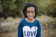 Portrait of girl standing in forest - CAVF58404