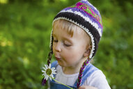 Portrait of little girl wearing knitted hat  blowing flower - PSIF00178