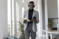 Portrait of young businessman with headphonbes and notebook in the office looking at cell phone - GRSF00017