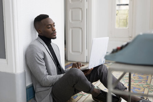 Portrait of young businessman sitting on the floor in the office working on laptop - GRSF00023