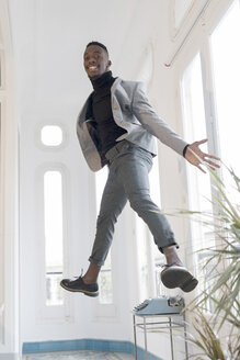 Portrait of smiling young businessman jumping in the air in his office - GRSF00026