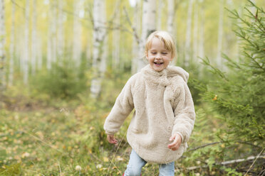 Portrait of laughing blond girl playing in autumnal forest - PSIF00183