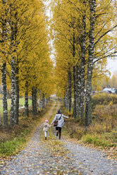 Finland, Kuopio, back view of mother and little daughter running side by side in autumn - PSIF00186