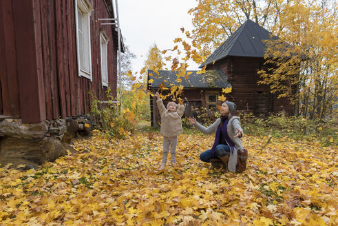 Finland, Kuopio, mother and little daughter throwing autumn leaves in the air - PSIF00189