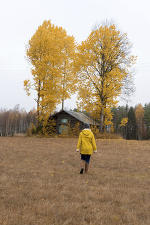 Finland, Kuopio, back view of woman in yellow rain jacket walking towards autumnal trees - PSIF00195