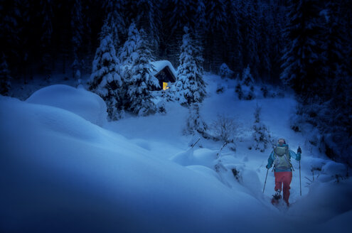 Austria, Salzburg State, snowshoeing, woman near hut at night - HHF05569