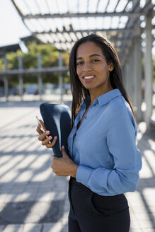 Businesswoman with smartphone, laptop bag - MAUF01833
