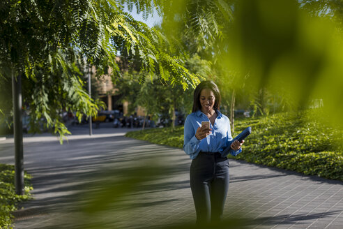 Businesswoman using smartphone, holding laptop bag in park - MAUF01851