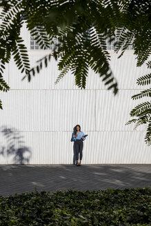 Businesswoman using smartphone, laptop bag - MAUF01854
