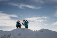 Low angle view of siblings on snow against sky - CAVF58479