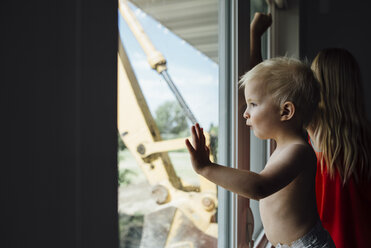 Side view of shirtless baby boy looking through window while standing by sister at home - CAVF58494