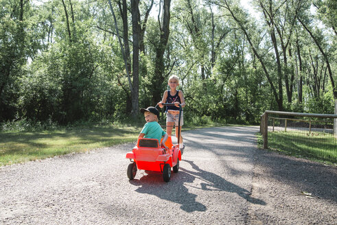 Girl pushing brother sitting in toy car at park - CAVF58503