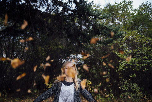 Playful girl throwing autumn leaves while standing at park - CAVF58506