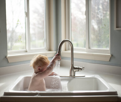 Cute baby boy holding faucet while sitting in kitchen sink against windows at home - CAVF58518
