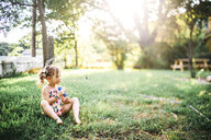 Full length of girl with popsicle sitting on grassy field at backyard - CAVF58560