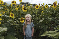 Cheerful girl standing amidst sunflowers at farm - CAVF58581