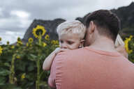 Rear view of father carrying son while standing in sunflowers farm - CAVF58587