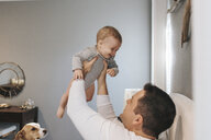 Father playing with son while sitting on bed at home - CAVF58593