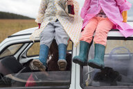Low section of siblings sitting on car roof - CAVF58605