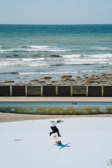 High angle view of man skateboarding at park by sea - CAVF58620
