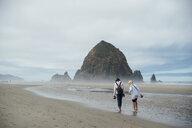 Full length of girls walking on shore at beach against cloudy sky - CAVF58680