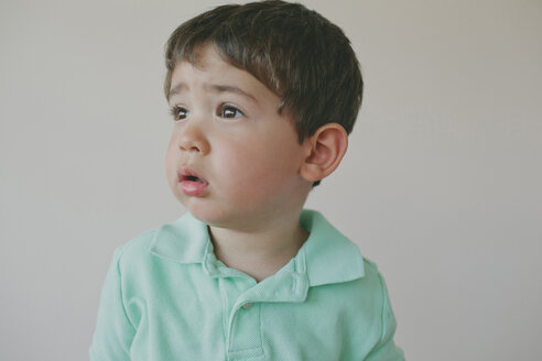 Thoughtful baby boy looking away against gray background - CAVF58752