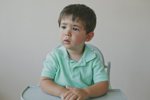 Thoughtful baby boy looking away while sitting on high chair against gray background - CAVF58755