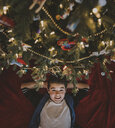 Overhead portrait of boy with hands behind head lying by Christmas tree at home - CAVF58773