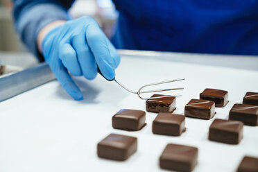 Midsection of chef holding chocolate dipped with fork in tray - CAVF58803