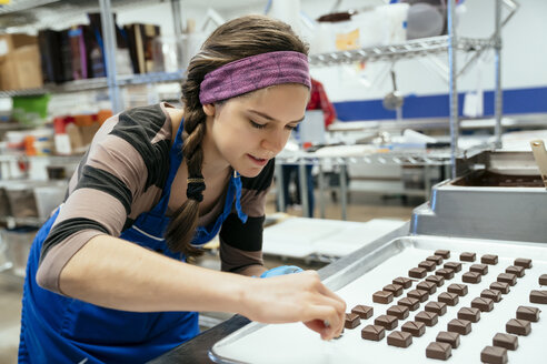 Female chef arranging chocolate pieces in tray at factory - CAVF58806