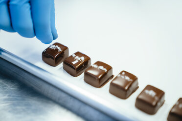 Cropped hand of chef garnishing chocolate pieces in tray at factory - CAVF58812
