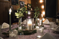Close-up of lit candles decorated on dining table at home - CAVF58818