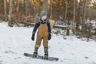 Boy snowboarding on snow covered field in forest - CAVF58866