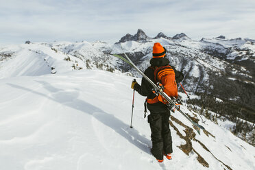 Rear view of hiker with backpack and ski standing on snowcapped mountain - CAVF58878