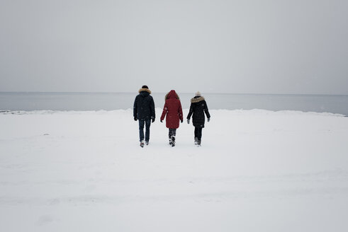 Rear view of friends walking on snow covered beach against sky - CAVF58893