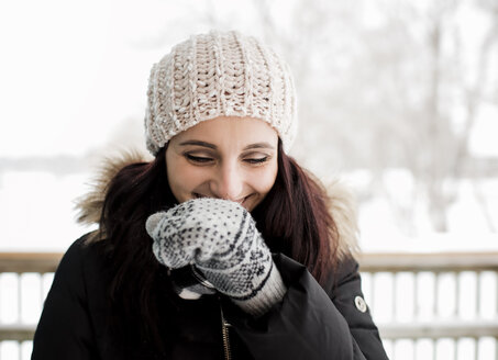 Smiling woman standing against sky during winter - CAVF58899
