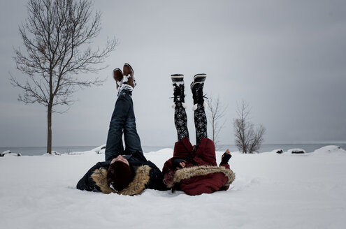 Friends lying at snow covered beach against sky during winter - CAVF58902
