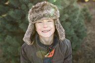 Portrait of smiling boy wearing warm clothing against Christmas Tree at farm - CAVF58917
