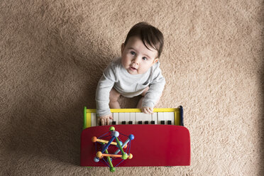 Overhead portrait of cute baby boy playing toy piano on carpet at home - CAVF58920