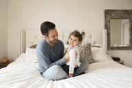 Portrait of cheerful daughter with father sitting on bed at home - CAVF58926