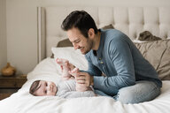 Father playing with son while sitting on bed at home - CAVF58929