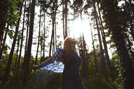 Carefree woman holding shirt while standing amidst trees at forest - CAVF58938