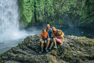 Portrait of happy family sitting on rocks against waterfall at forest - CAVF58974