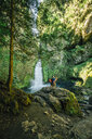 Family standing on rocks against waterfall at forest - CAVF58977