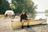 Portrait of mid adult man sitting on boat with friends in background at campsite - CAVF59004