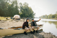 Male friends talking while sitting on boat at campsite by lake - CAVF59013