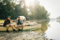 Male friends sitting on boat at lakeshore - CAVF59016